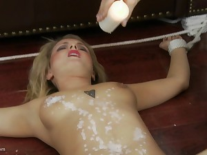 Blondie loves wax play while she is tied to the floor